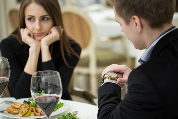 Jovem mulher fazendo um gesto de expressão exasperada em um encontro ruim no restaurante