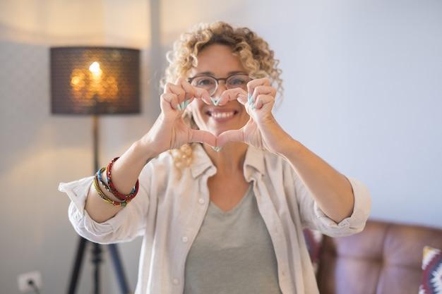 Jovem mulher fazendo um gesto de formato de coração com as mãos. mulher bonita flertando e sorrindo para a câmera. mulher atraente e alegre fazendo um símbolo em forma de coração usando as mãos em casa