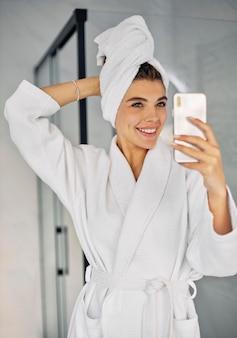 Jovem mulher fazendo um show de beleza com seu telefone