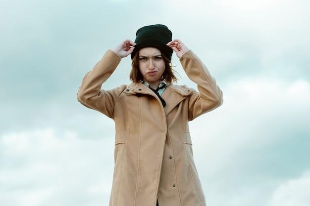 Jovem mulher fazendo uma careta de zombaria e piada, em um céu. juventude