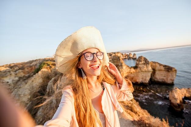 Jovem mulher fazendo uma selfie na costa rochosa durante o nascer do sol em uma viagem em lagos, no sul de portugal