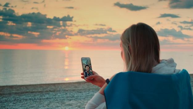 Jovem mulher fazendo videochamada para a amiga com o smartphone na praia, relaxando e falando com ...