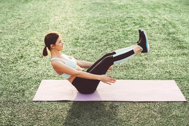 Jovem mulher fazendo yoga no estádio