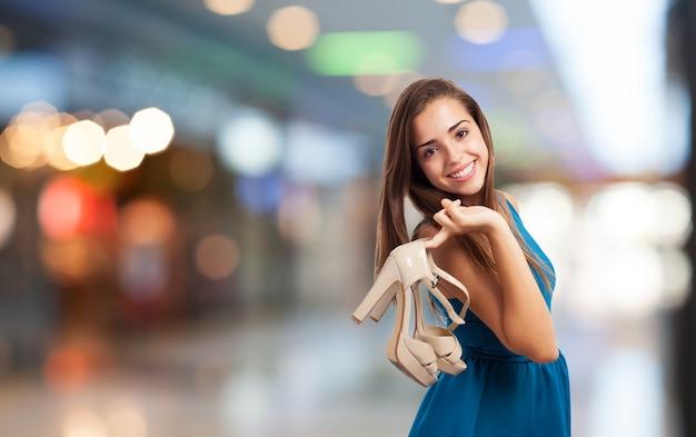 Jovem mulher fazer compras com saltos altos no centro comercial
