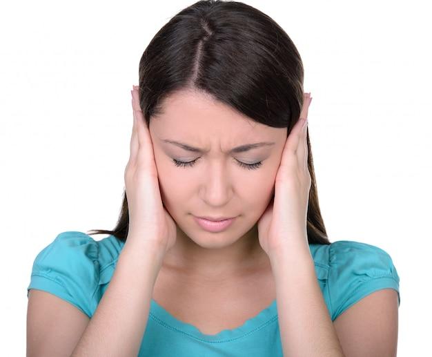 Jovem mulher fechando os ouvidos com as mãos.