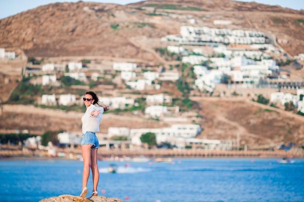 Jovem mulher feliz à beira de um precipício com maravilhosa vista da antiga pequena aldeia em mykonos, grego