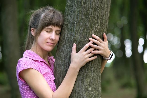 Jovem mulher feliz abraçando o tronco de uma árvore grande no parque de verão.