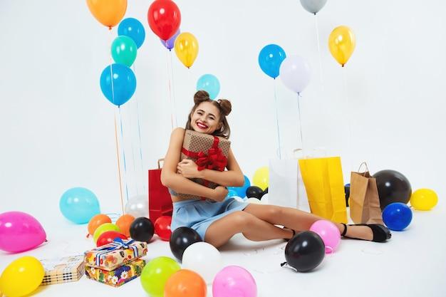 Jovem mulher feliz abraçando presentes sentado no chão após a celebração