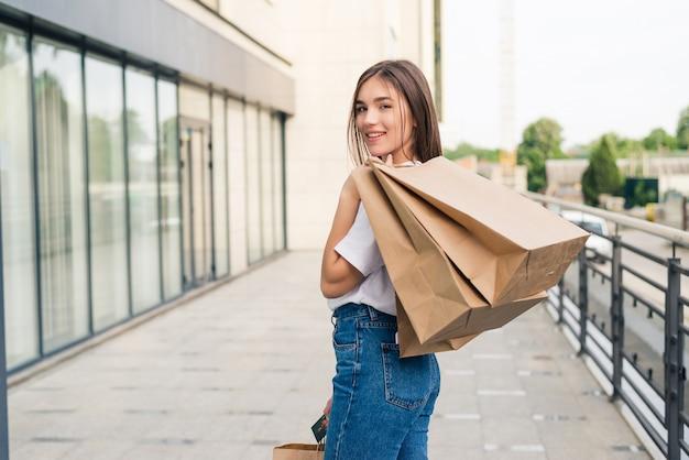 Jovem mulher feliz andando com sacolas de compras ao ar livre na rua