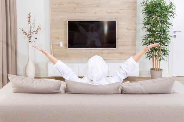 Jovem mulher feliz animada assistindo televisão