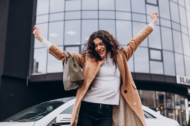 Jovem mulher feliz ao lado do carro