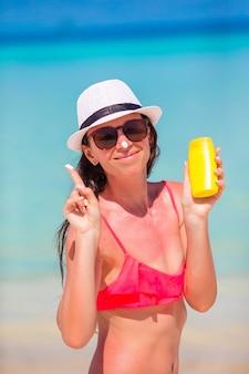 Jovem mulher feliz aplicando loção bronzeadora no nariz na praia branca