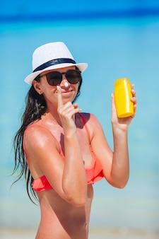 Jovem mulher feliz aplicando protetor solar no nariz na praia branca