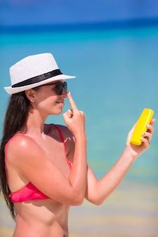 Jovem mulher feliz aplicar loção bronzeadora no nariz na praia branca