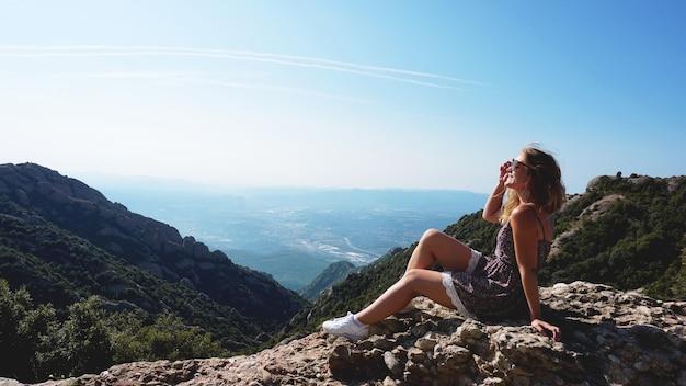 Jovem mulher feliz apreciando a vista magnífica das montanhas de montserrat