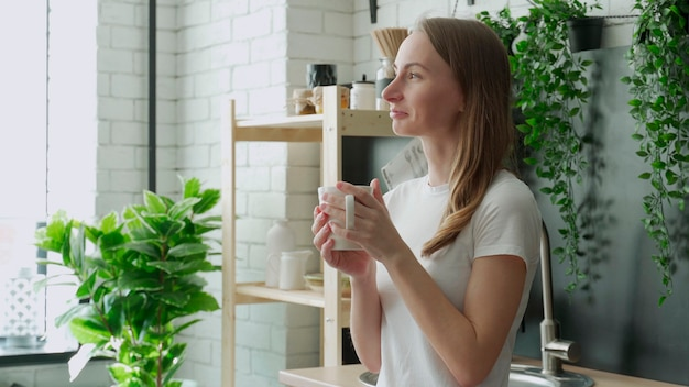 Jovem mulher feliz bebe café na cozinha pela manhã em casa