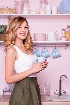 Jovem mulher feliz bebendo café ou chá em casa na cozinha.