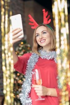 Jovem mulher feliz bebendo champanhe e tomando selfie na festa de ano novo