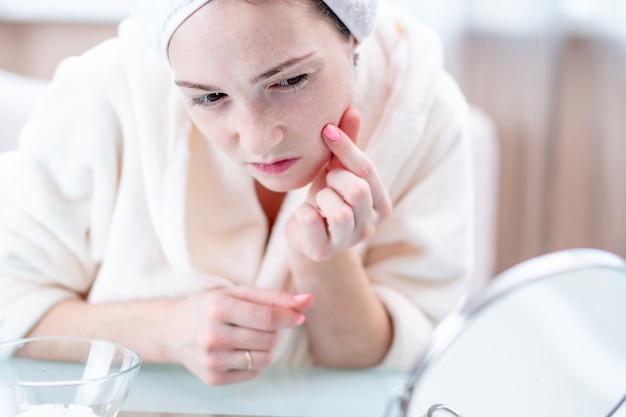 Jovem mulher feliz bonita com uma toalha na cabeça que olha sua pele em um espelho. higiene e cuidados oportunos para a pele