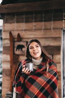 Jovem mulher feliz caucasiana em uma manta está bebendo uma bebida quente no quintal, aproveitando a manhã de natal.