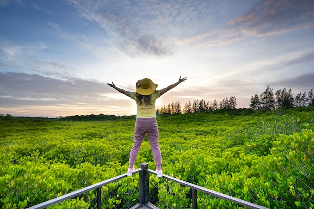 Jovem mulher feliz com as mãos a subir na bela paisagem de floresta de mangue com linda