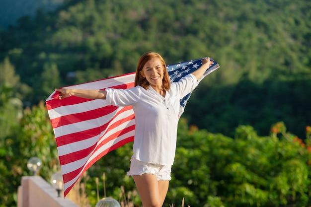 Jovem mulher feliz com bandeira dos estados unidos, apreciando o pôr do sol na natureza.