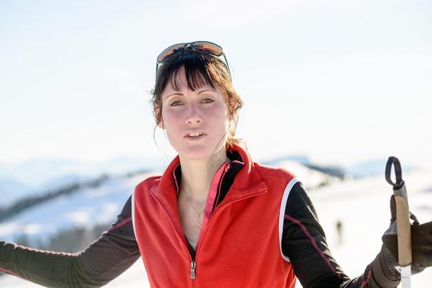 Jovem mulher feliz com bastões de esqui no esqui no inverno