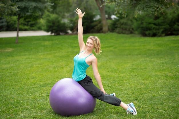 Jovem mulher feliz com bola de fitness, ao ar livre