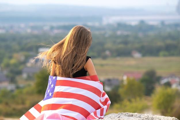 Jovem mulher feliz com cabelo comprido, segurando acenando na bandeira nacional americana do vento em seus ombros descansando ao ar livre, aproveitando o dia quente de verão.