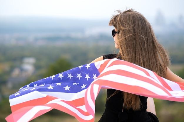 Jovem mulher feliz com cabelo comprido, segurando acenando na bandeira nacional americana do vento em seus sholders descansando ao ar livre, aproveitando o dia quente de verão.