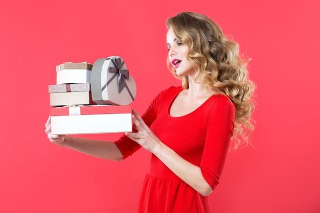 Jovem mulher feliz com caixas de presente isoladas sobre fundo vermelho. expressões faciais expressivas.