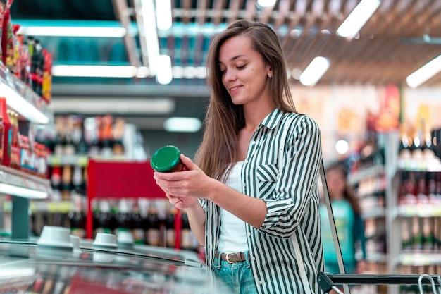 Jovem mulher feliz com carrinho de compras escolhe, verificando o rótulo de produtos e comprando comida no supermercado