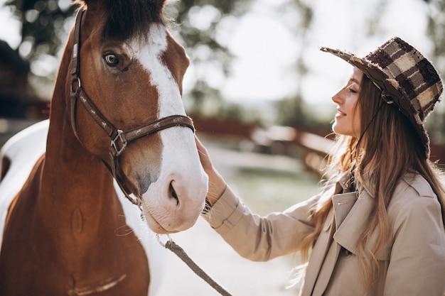 Jovem mulher feliz com cavalo no rancho