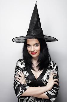 Jovem mulher feliz com chapéu de bruxa