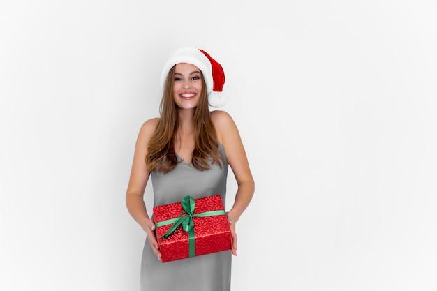 Jovem mulher feliz com chapéu de papai noel segurando um presente de natal enquanto fica em pé na celebração de um fundo branco