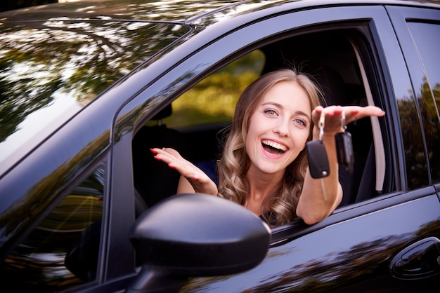 Jovem mulher feliz com chaves no automóvel.