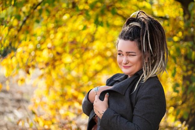 Jovem mulher feliz com dreadlocks ao ar livre no outono, conceito de cultura jovem