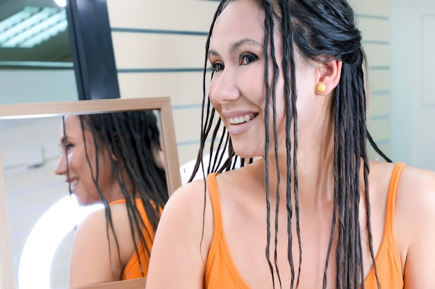 Jovem mulher feliz com dreadlocks. dreadlocks falsos no modelador. reflexo no espelho