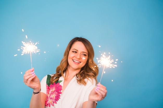 Jovem mulher feliz com estrelinhas comemorando e rindo na parede azul