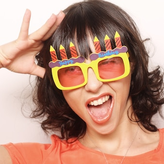 Jovem mulher feliz com grandes óculos de sol laranja