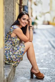 Jovem mulher feliz com olhos azuis que sorri sentando-se na etapa urbana.