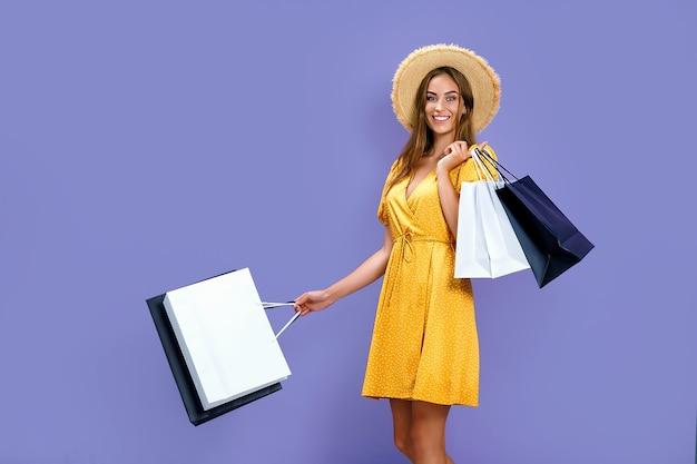 Jovem mulher feliz com pacotes depois de fazer compras em fundo roxo com descontos conceito de sexta-feira negra