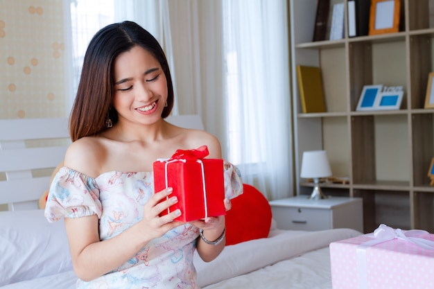 Jovem mulher feliz com presente vermelho no quarto