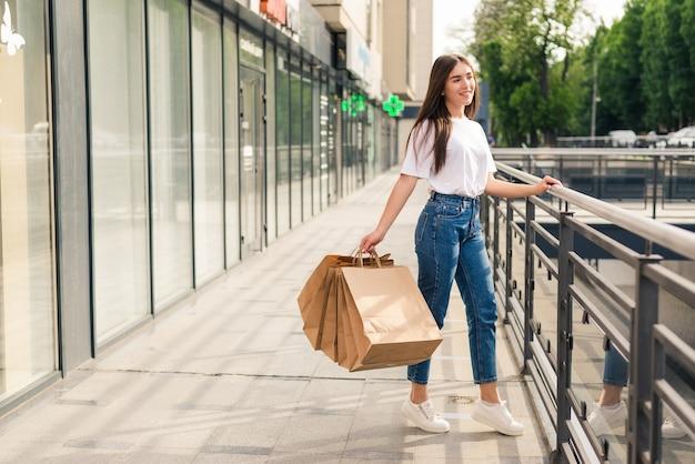 Jovem mulher feliz com sacolas de compras, andando na rua da loja.