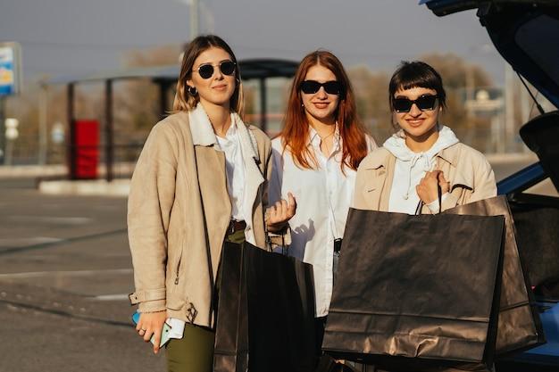 Jovem mulher feliz com sacolas de compras, andando na rua.