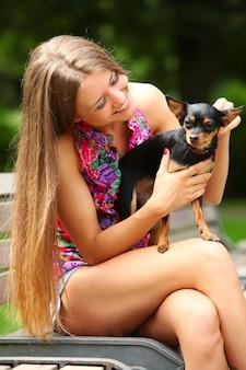 Jovem mulher feliz com seu cachorro fofo