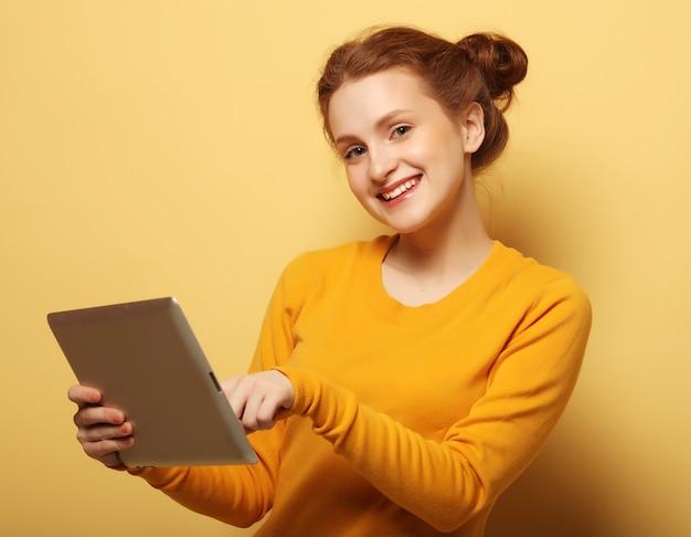 Jovem mulher feliz com tablet pc sobre fundo amarelo