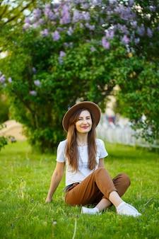 Jovem mulher feliz com um chapéu senta-se em um gramado verde em um parque. uma garota de aparência europeia com um sorriso no rosto em um dia ensolarado de verão