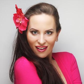 Jovem mulher feliz com uma flor rosa no cabelo
