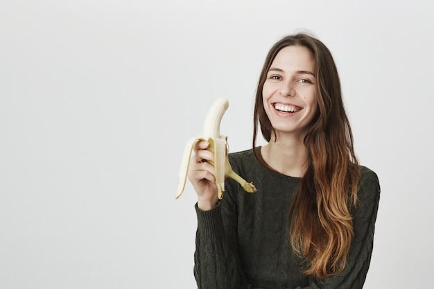 Jovem mulher feliz comendo banana e rindo